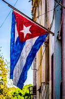 A Cuban Flag painted on canvas and displayed on the crumbling walls of Old Havana (La Habana), Cuba.
